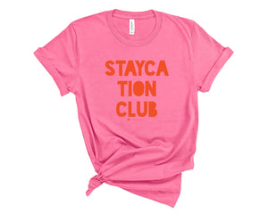 Deep Pink, crew neck t-shirt with Staycation Club in orange block lettering.