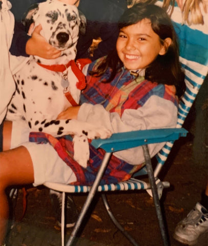 Axiology founder, Ericka Rodriguez, has always loved animals, poses with dog as a kid