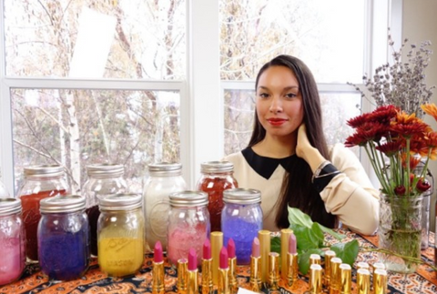 Axiology founder and CEO poses with pigments and lipsticks in the early days
