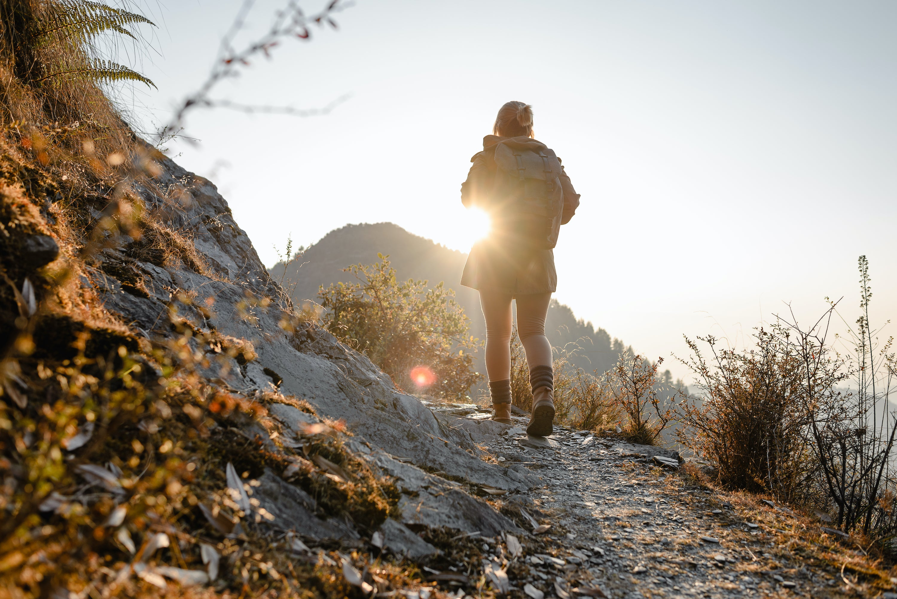 woman hiking path up mountain with backpack in sunshine