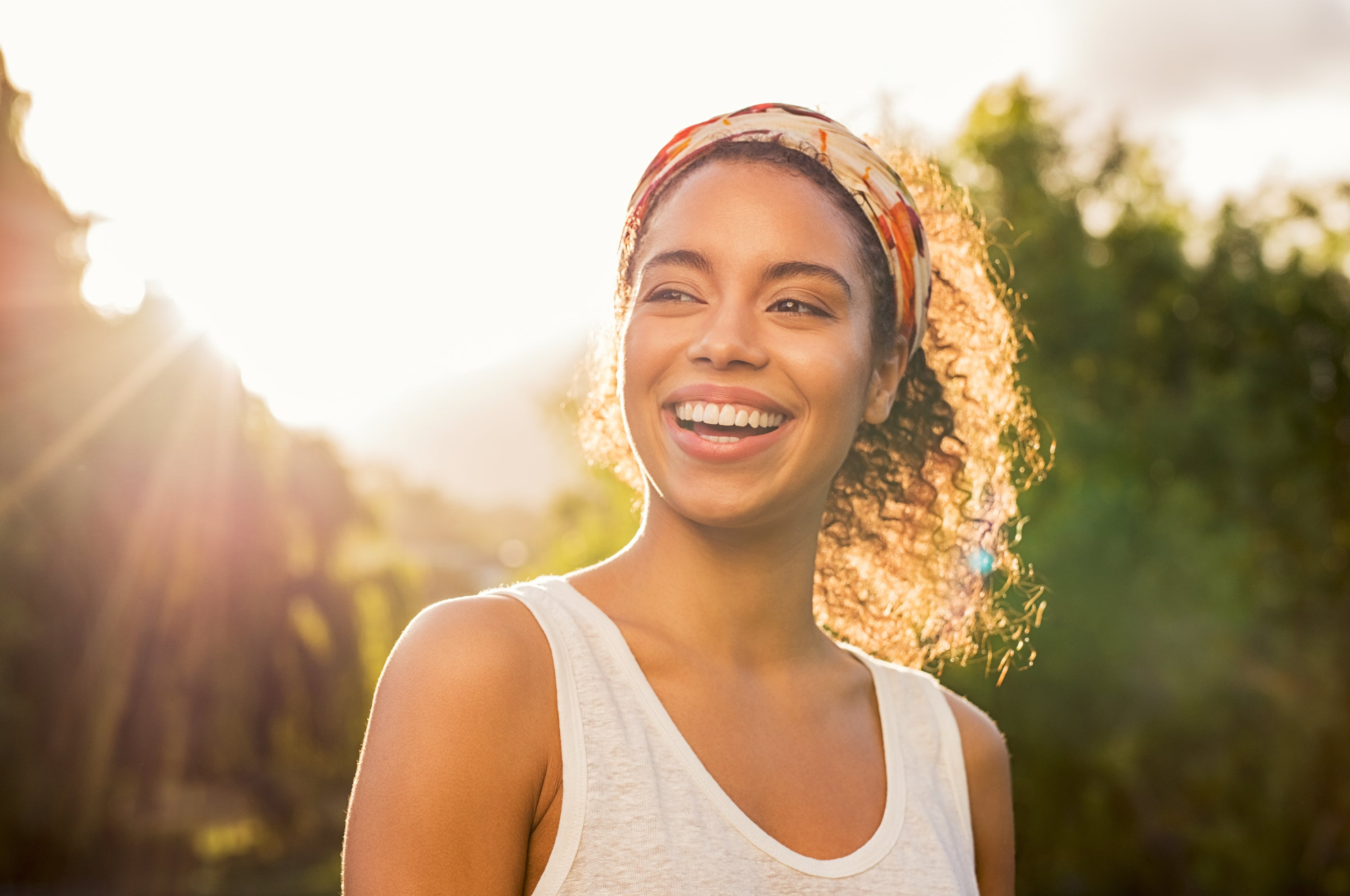 smiling girl with curly hair and headband in sunshine