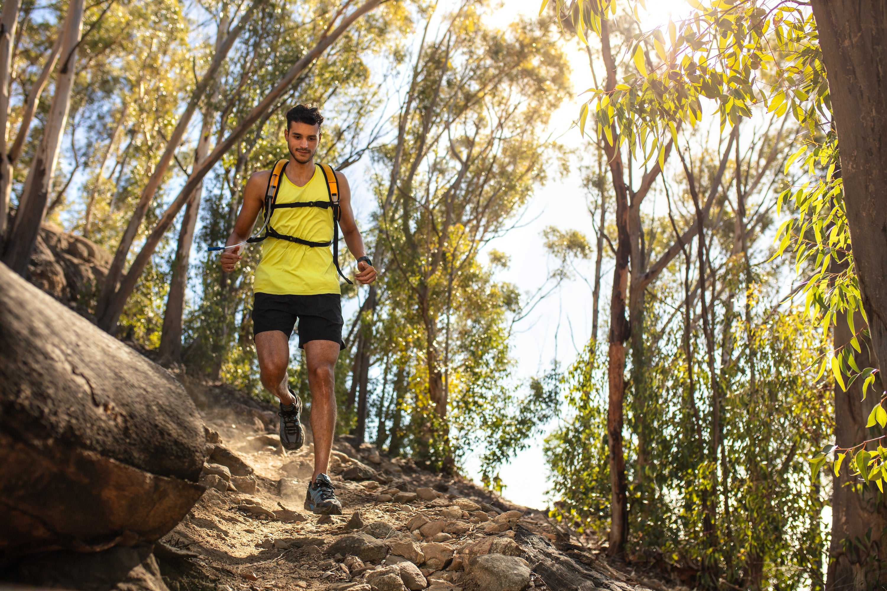 young fit man running down wooded trail with camelbak