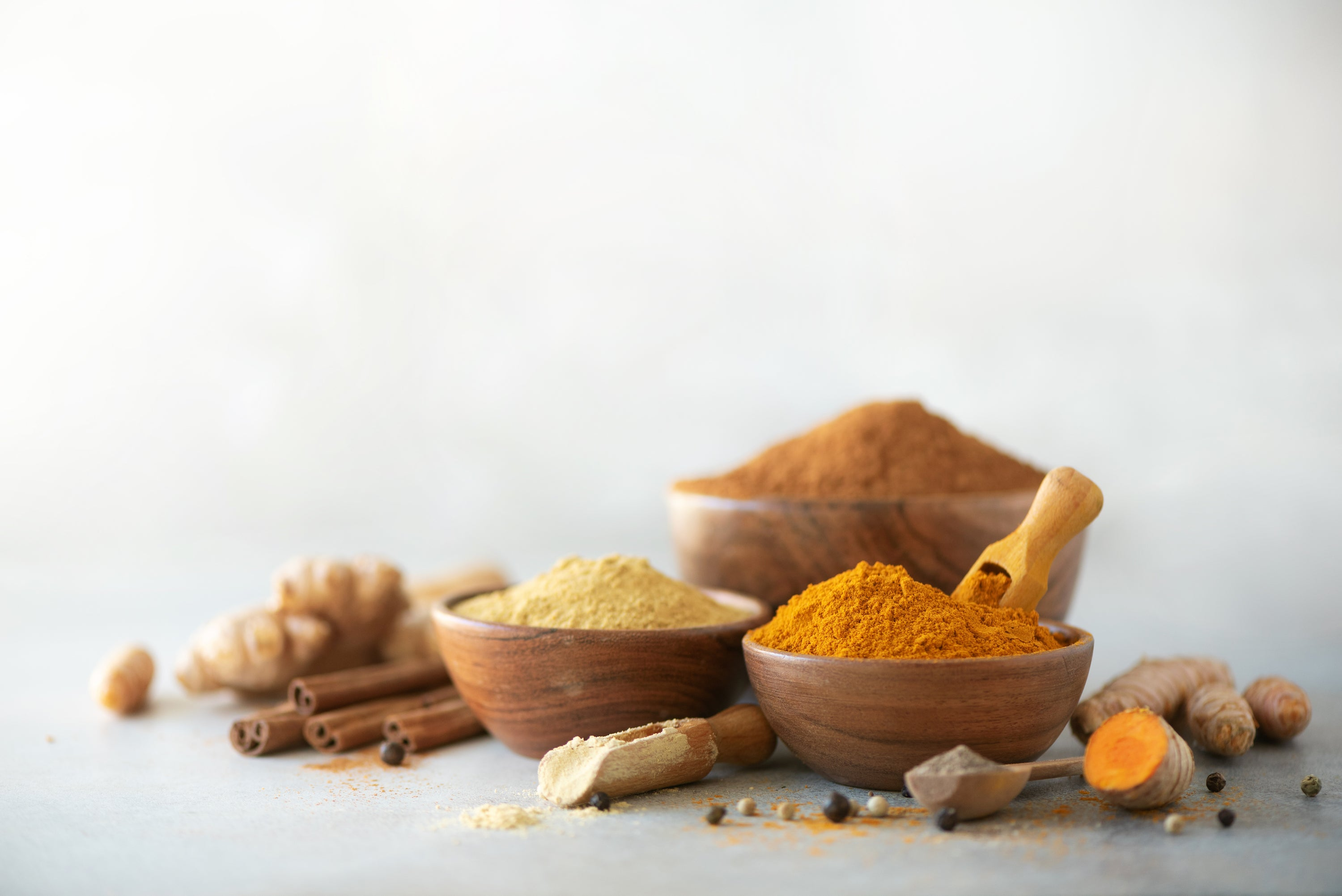ginger and turmeric ground in bowls with roots on table