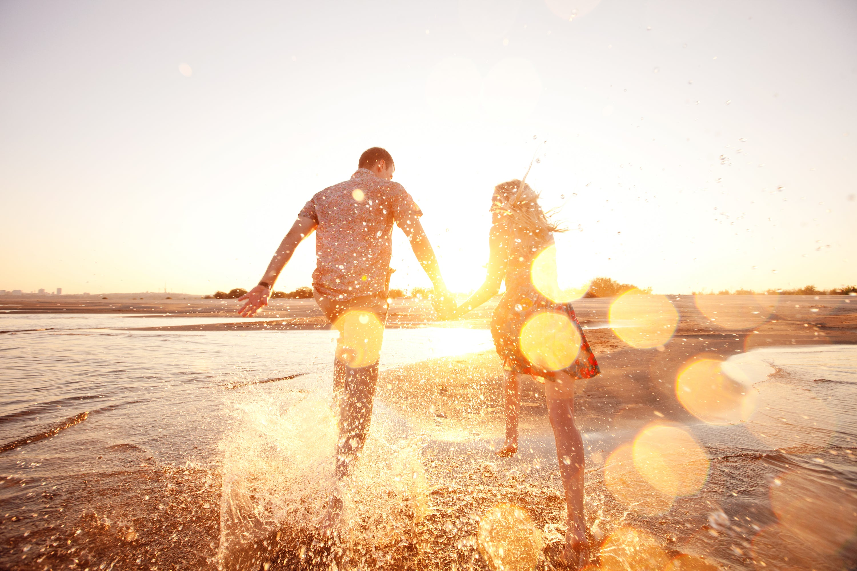man and woman holding hands running through shallow ocean water in sunshine