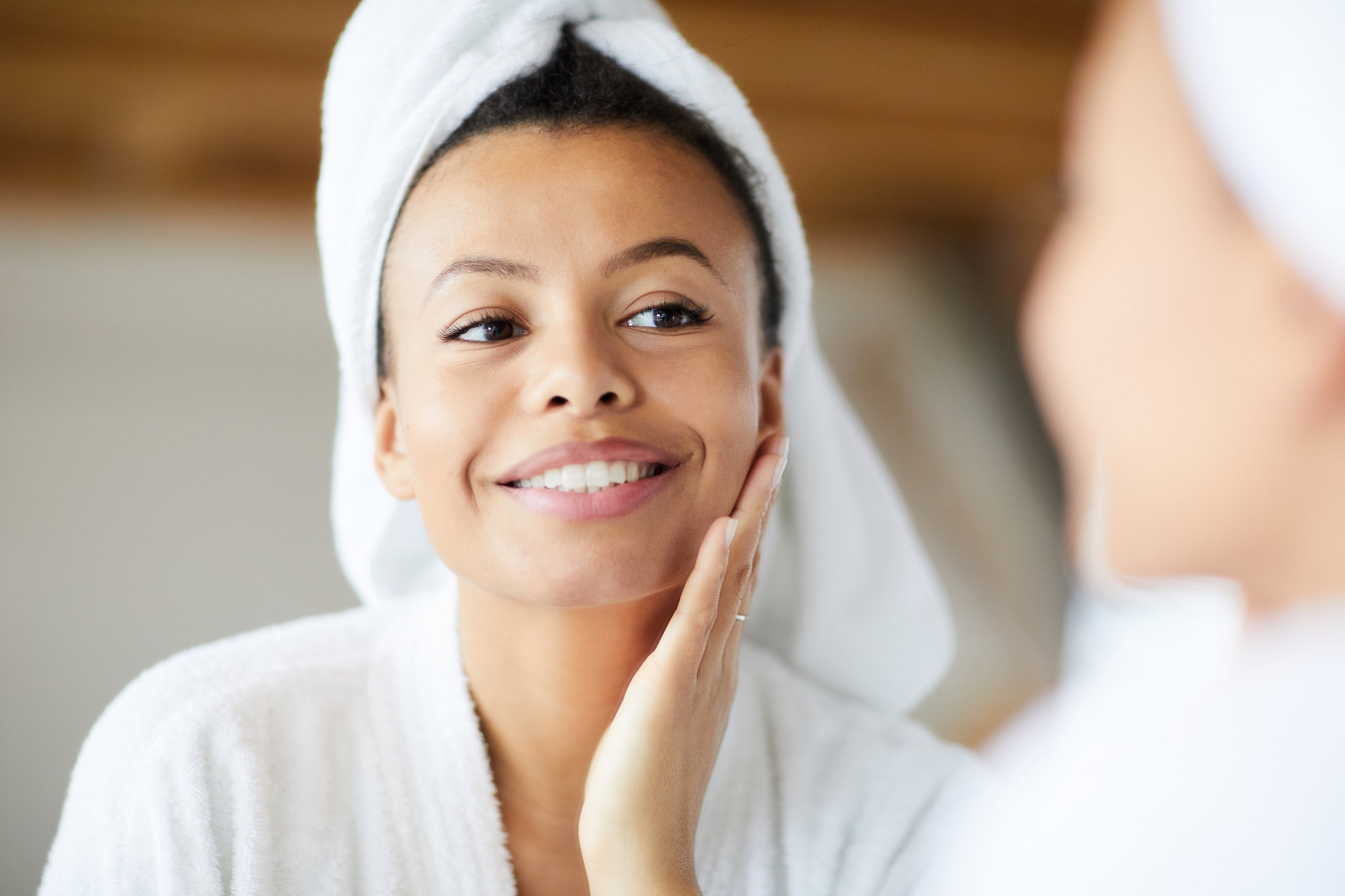 woman of color with clear skin touching cheek and looking in mirror with towel on head wearing bathrobe