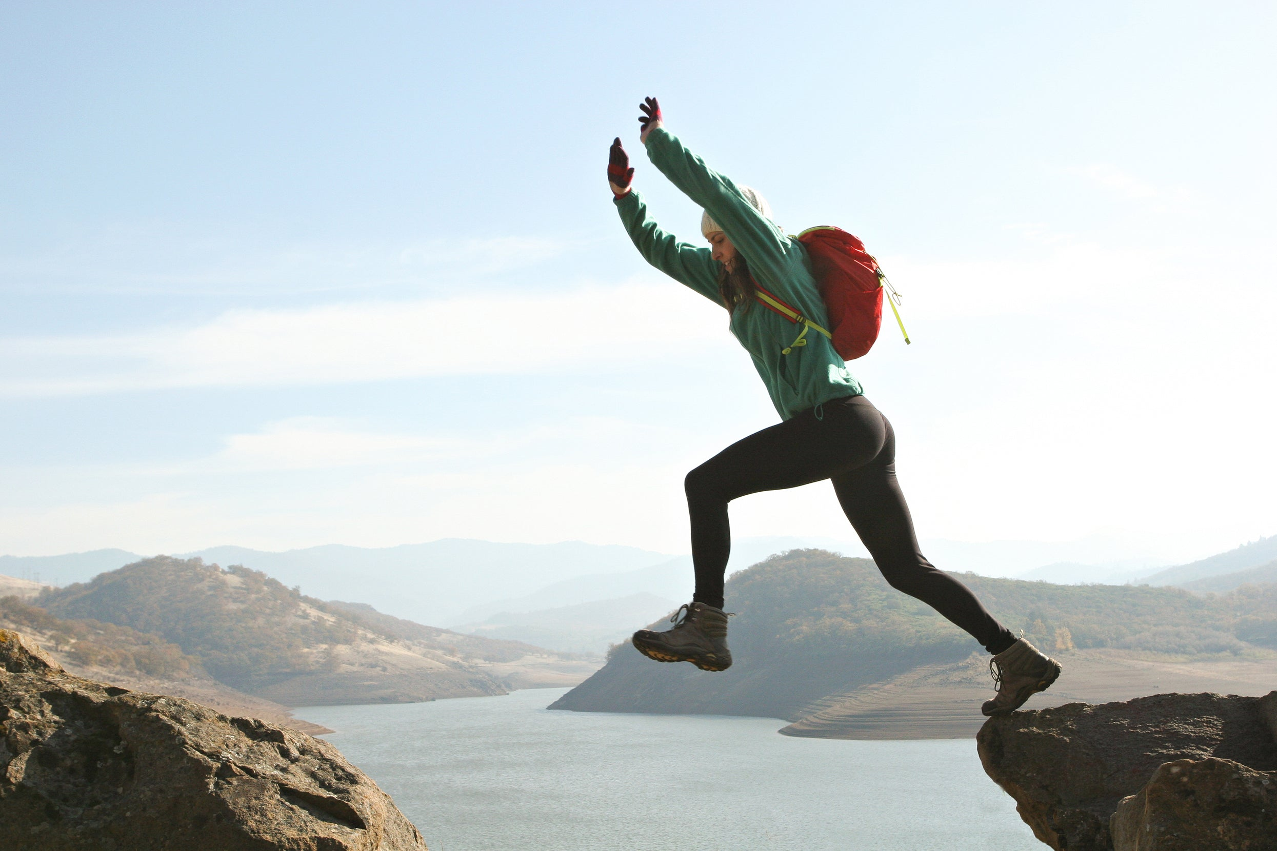 female hiker with backpack taking leap between two rocks with lake in background