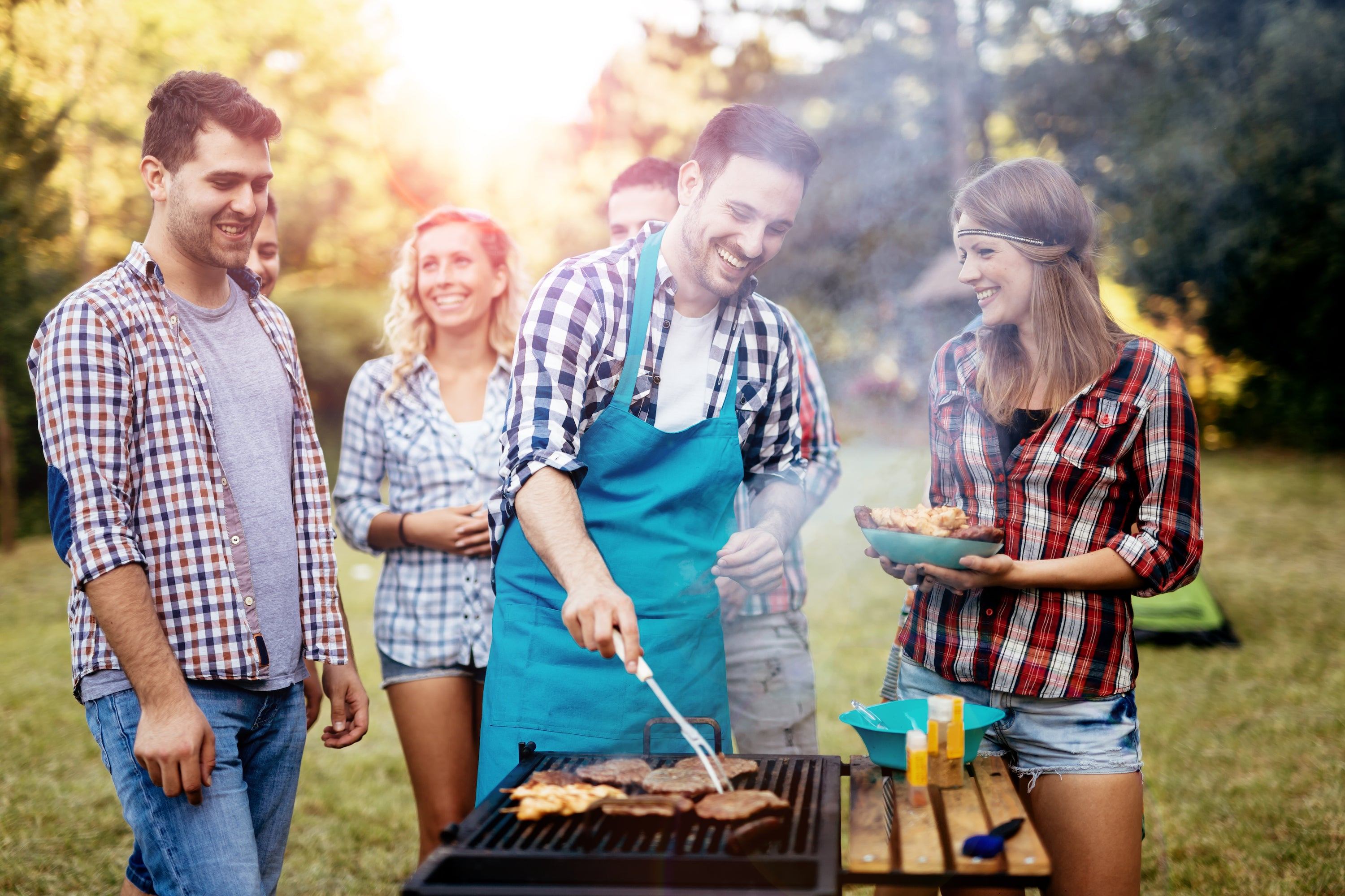 man grilling with friends waiting for food