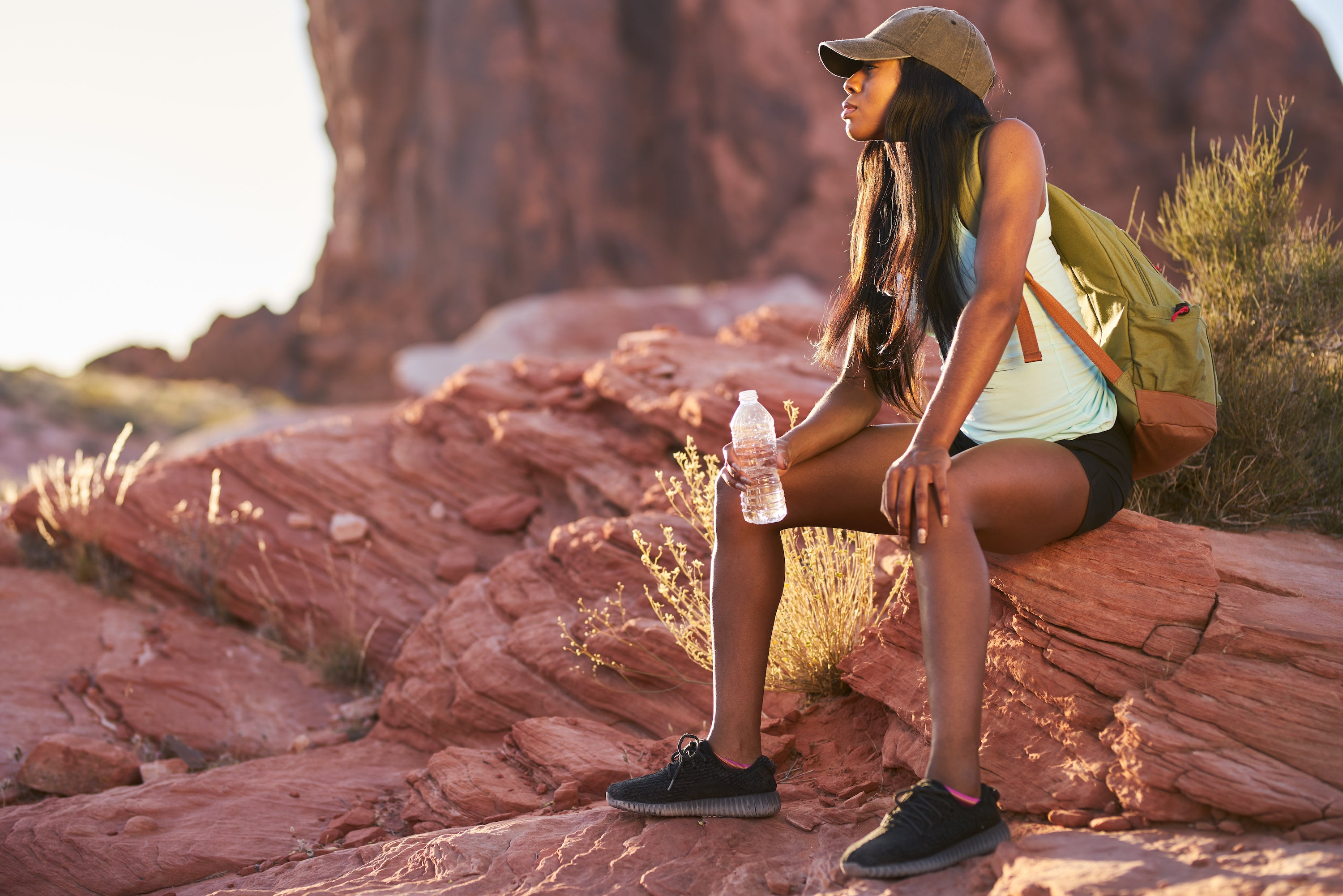 african american girl with hat and backpack sitting on red rock drinking water