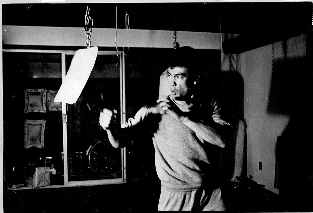 Black and white photo of Bruce Lee punching a bag inside his studio