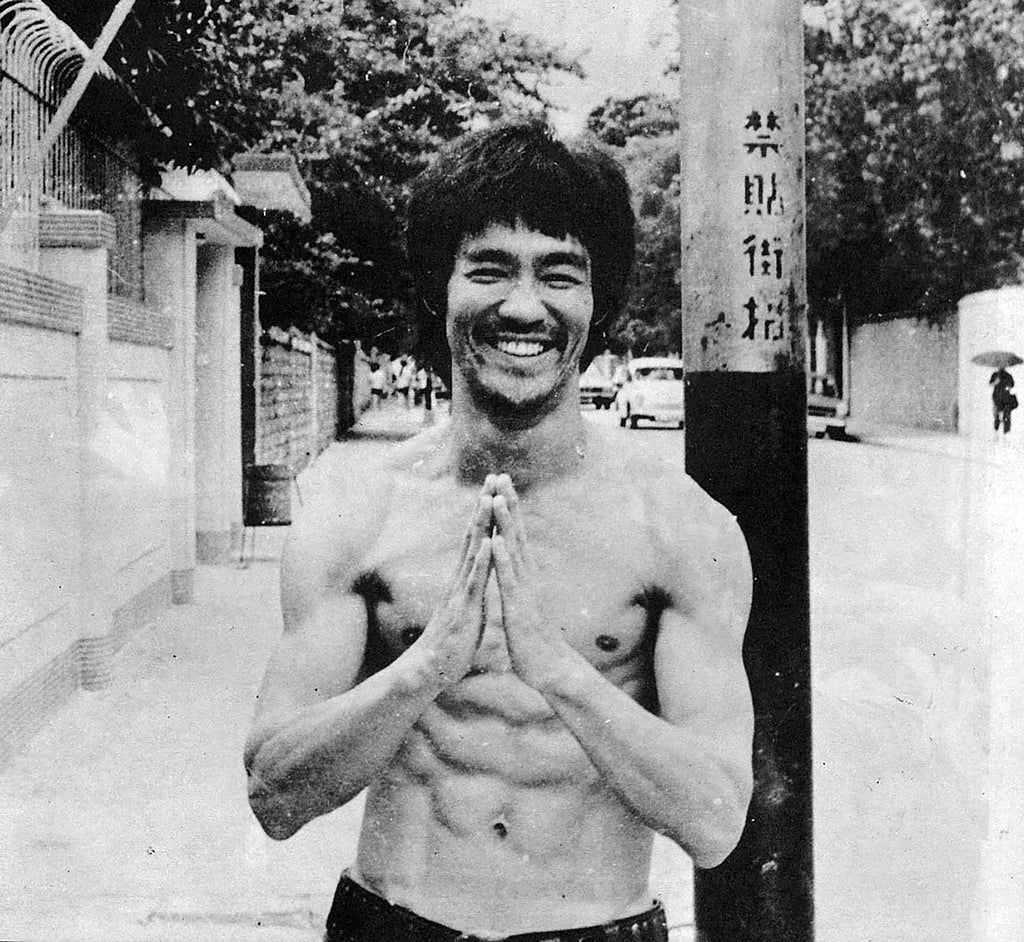 black and white photo of Bruce Lee with prayer hands