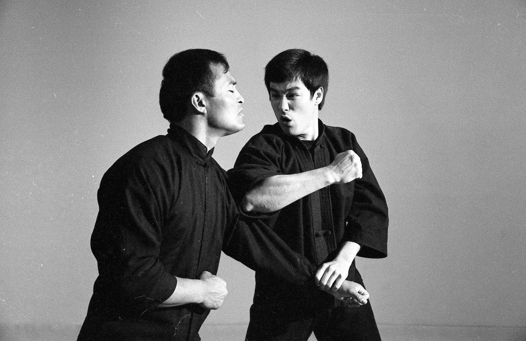 black and white photo of Bruce Lee fighting an opponent
