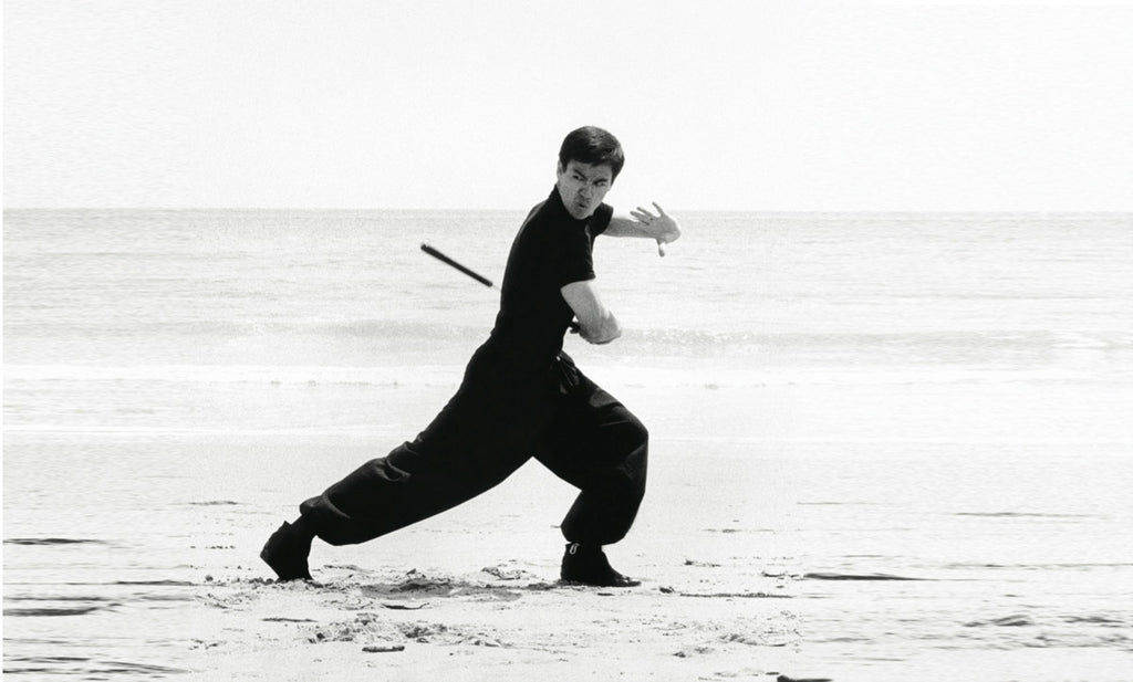 Bruce Lee practicing on beach in all black