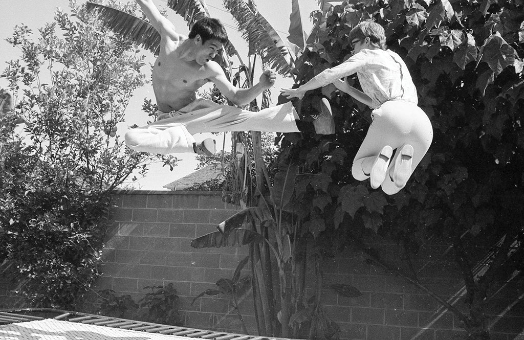 Bruce Lee jumping on a trampoline with his wife Linda Lee