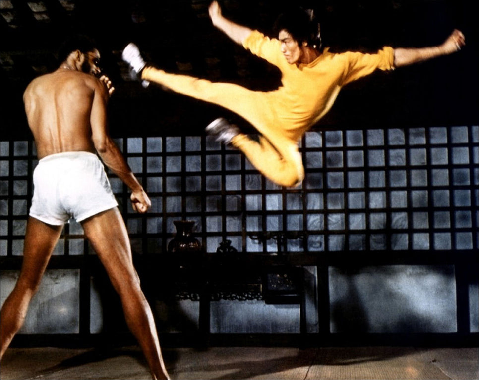 Bruce Lee kicking Kareem Abdul Jabbar while wearing a yellow jumpsuit in the 1978 movie Game of Death