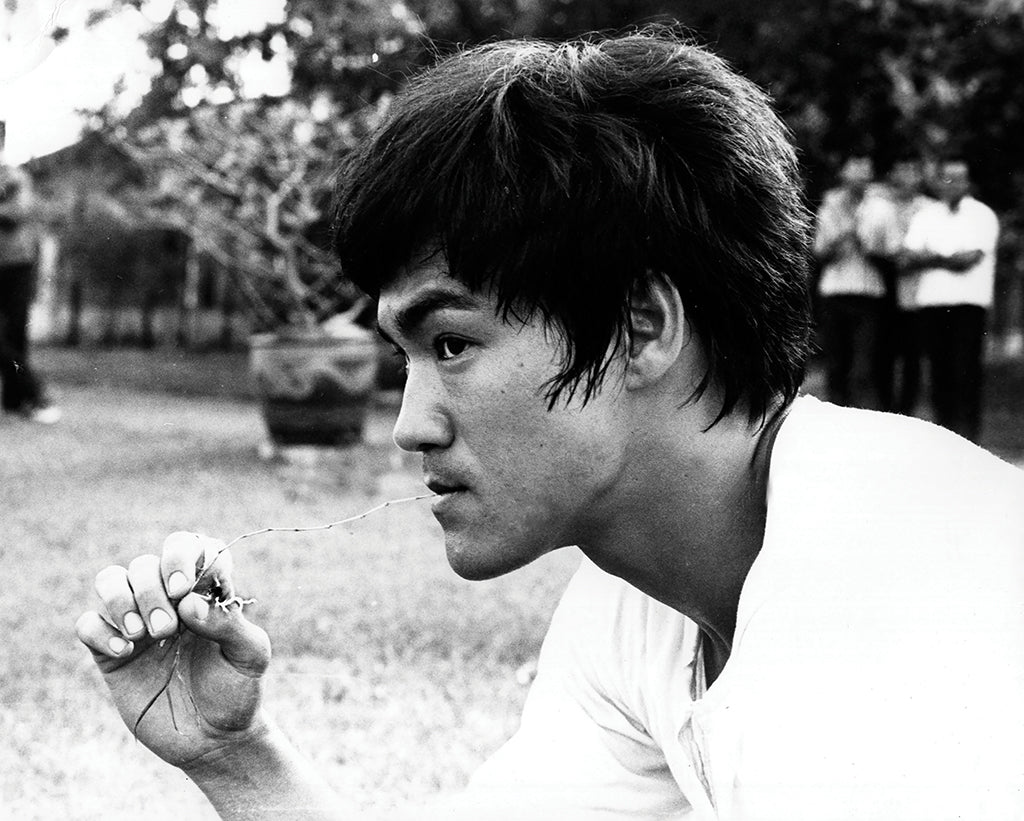 Black and white photo of actor Bruce Lee thinking in a field with hand raised