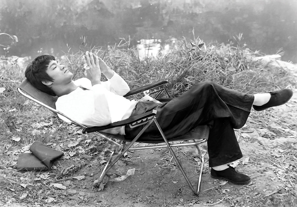Black and white photo of actor Bruce Lee reclining in a chair by the water