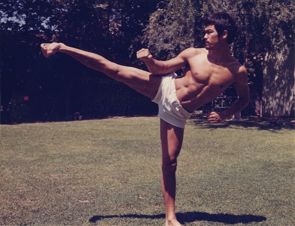 Bruce Lee with goatee in shorts in kick form