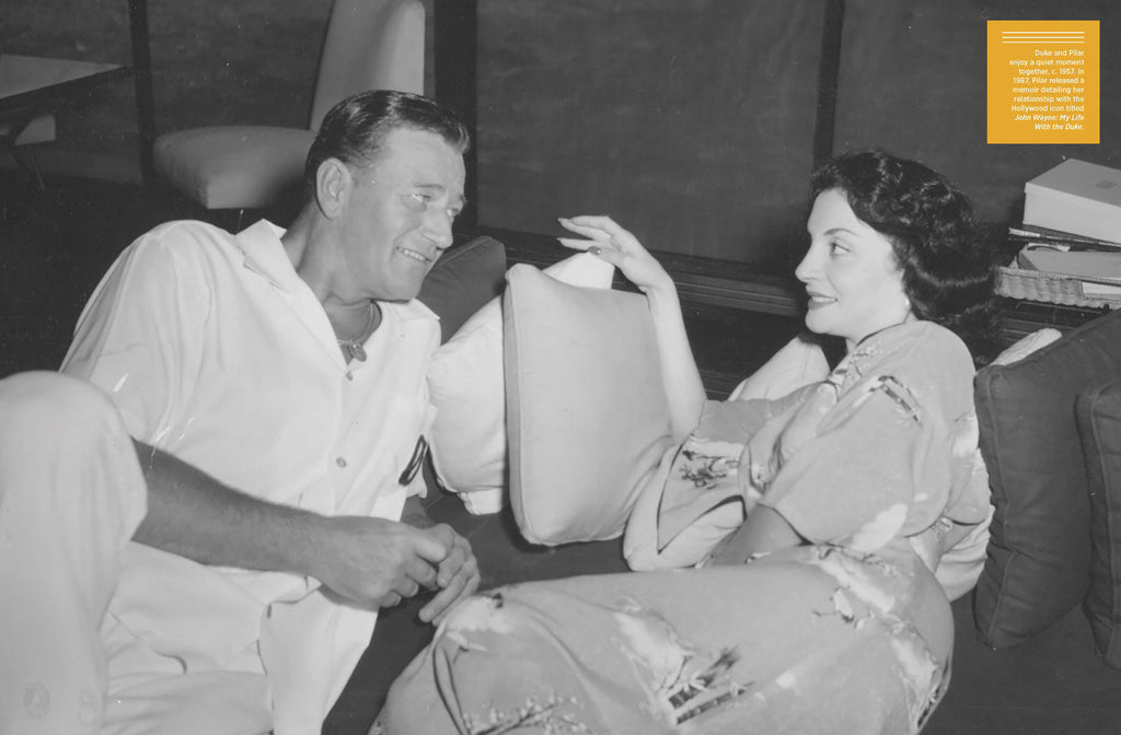John Wayne and wife Pilar lounge on couch