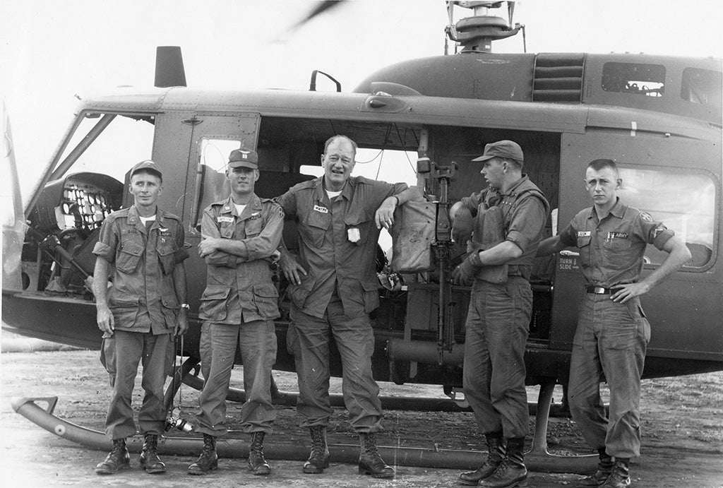 John Wayne posing with troops in Vietnam in front of a helicopter