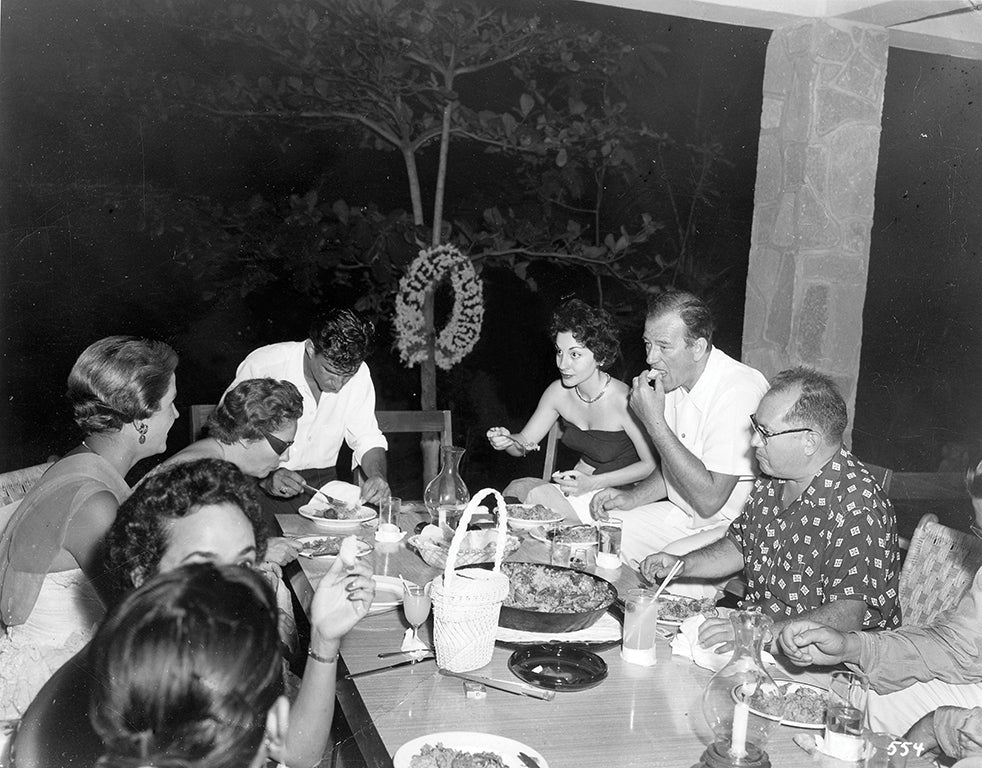 John Wayne and wife Pilar dining with friends