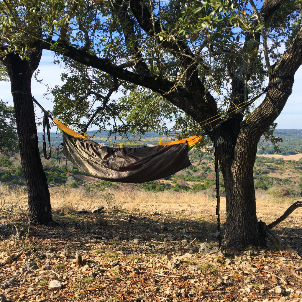 This hammock has a hammock underquilt hanging below it. The quilt hangs close to the hammock so that with the weight of the camper, the hammock will be nestled down inside the underquilt.