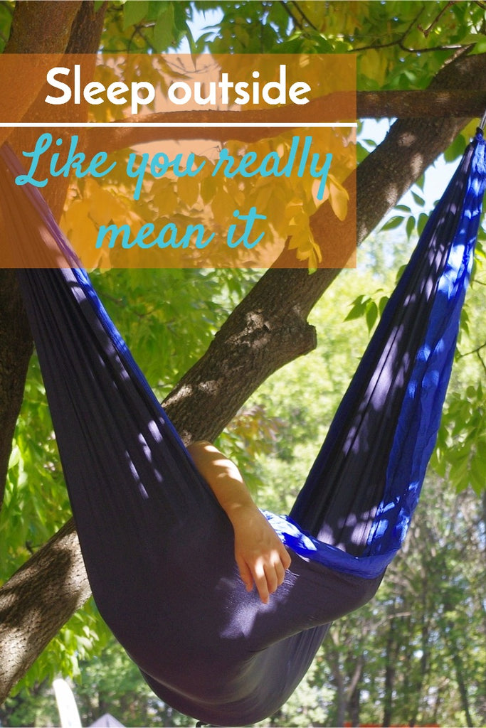 "Image of a person sleeping in a hammock while camping with quote ""sleep outside like you really mean it"""