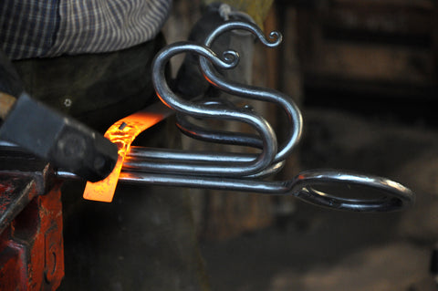 Forged collars that bound the legs and hooks are made by wrapping red hot steel around the piece and forge welding the band together