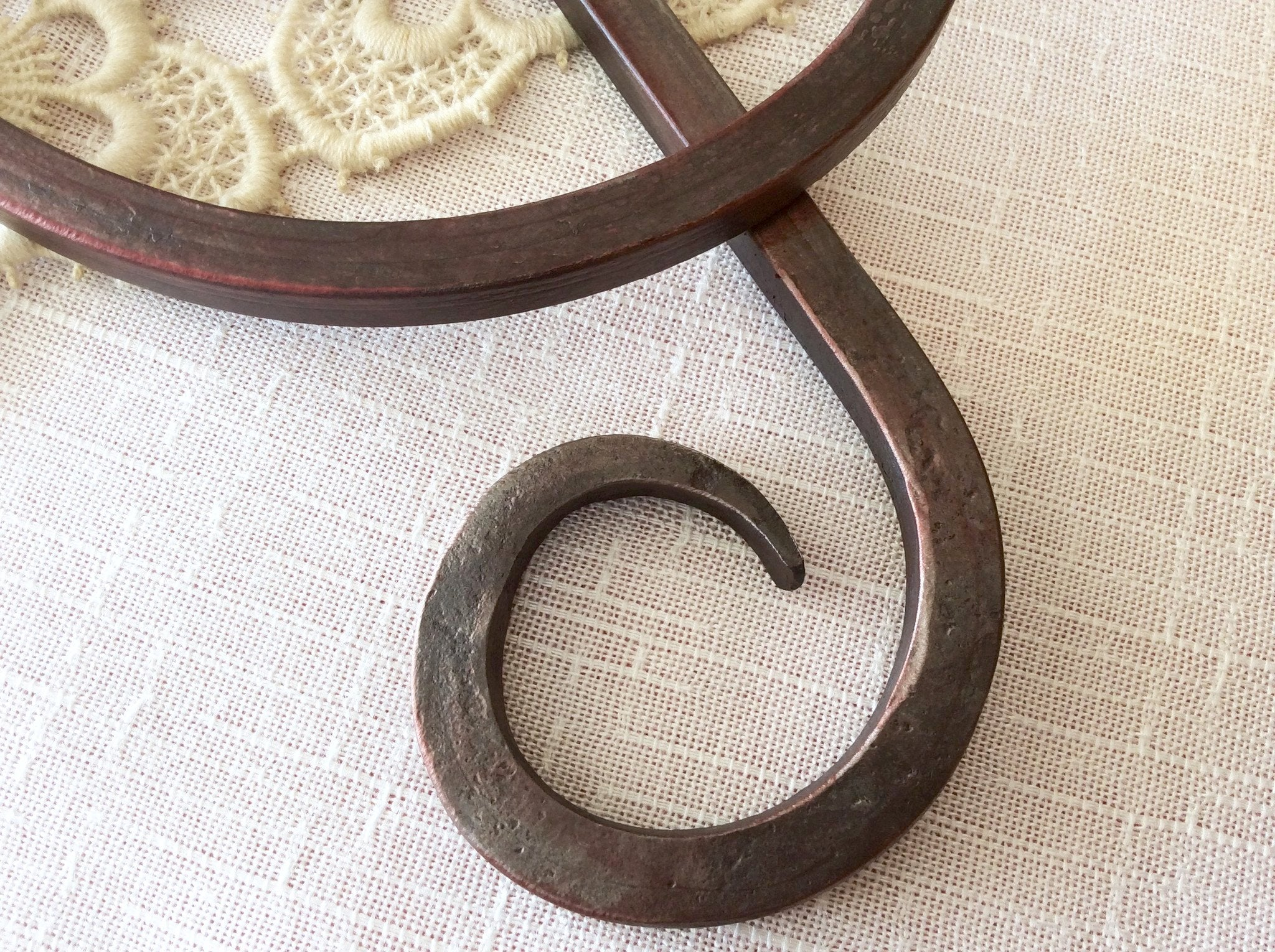 This tail of the forged iron treble clef shows the marks of the fire and hammer through the translucent red finish.
