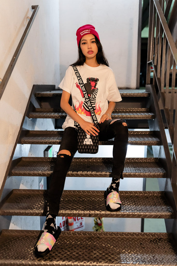 model wearing escape anime tee sitting on stairs