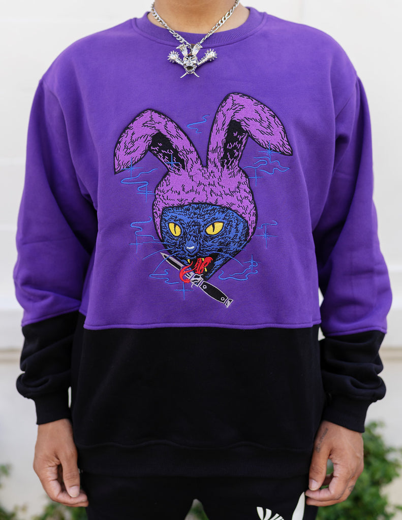 model wearing half purple and black crew neck sweatshirt with an embroidered cat with bunny ears and a knife in its mouth design