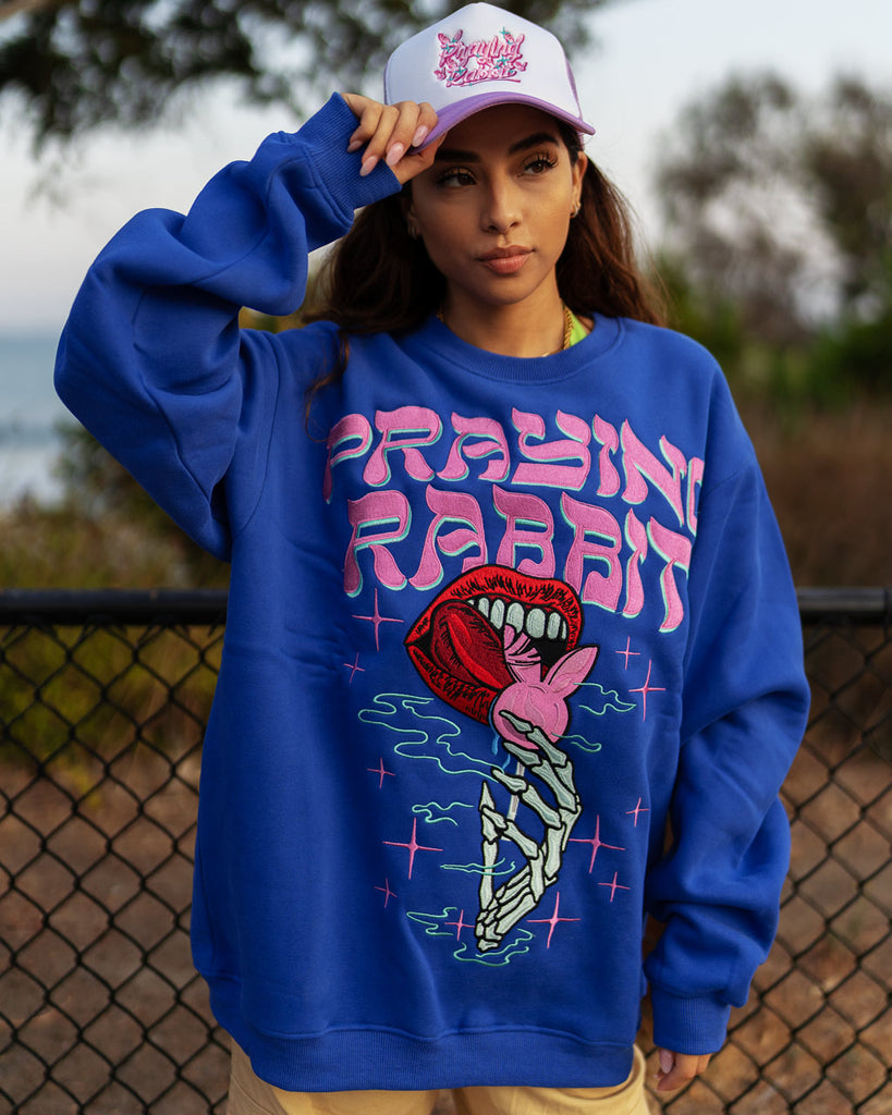 model wearing blue crew neck with a large embroidered skeleton hand holding a rabbit lollipop with lips licking it design