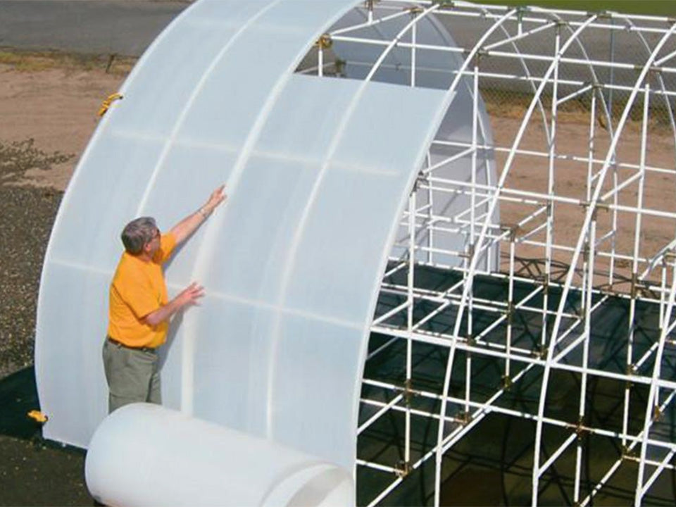 A man installing Solexx Greenhouse Covering Rolls