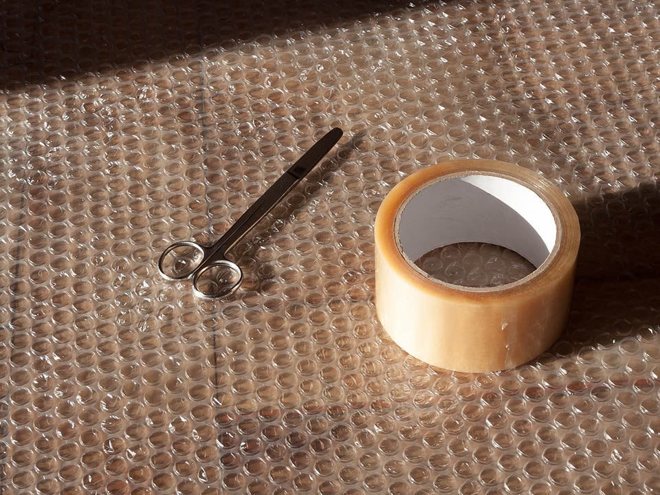 A bubble wrap with a scissor and scotch tape