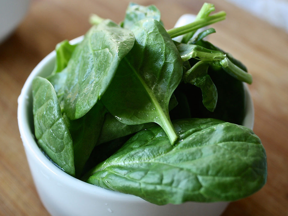 Spinach leaves in a white cup