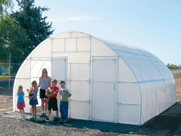 Solexx conservatory with a family in front - Greenhouses for Community Projects