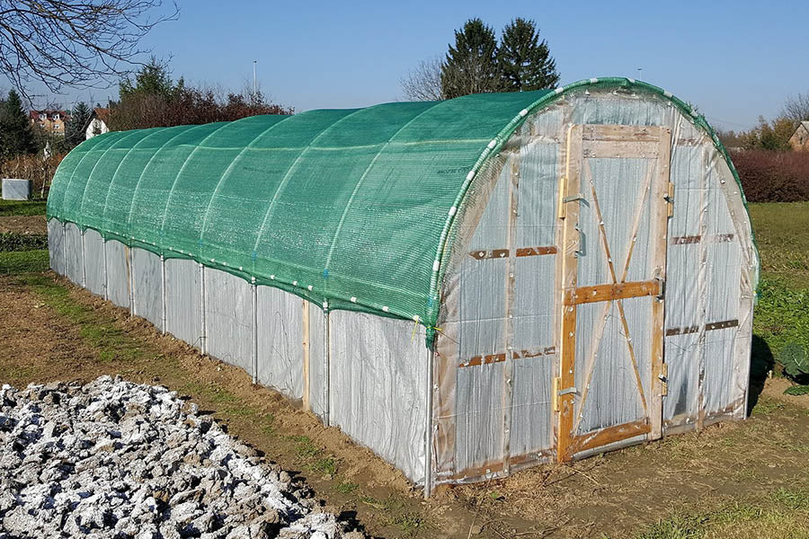 Windsor Combi greenhouse is a wooden greenhouse that is like a hoop house