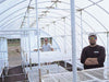 Image of 16ft x 8ft Conservatory Greenhouse - interior view showing framework -  a man standing inside