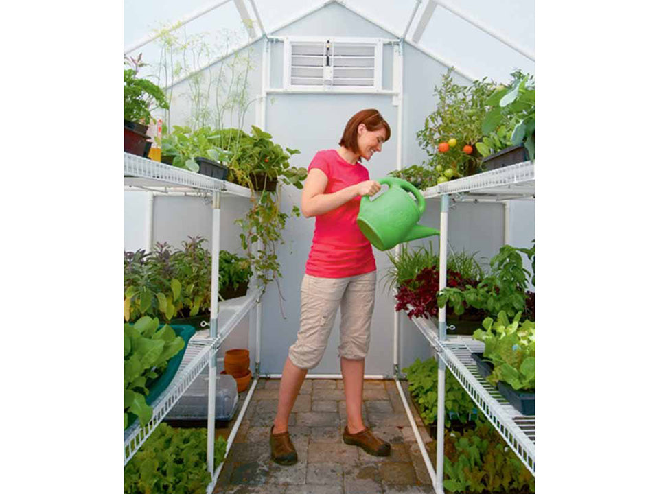 Solexx 8ft x 16ft Garden Master Greenhouse G-516 - interior view with a woman watering the plants inside