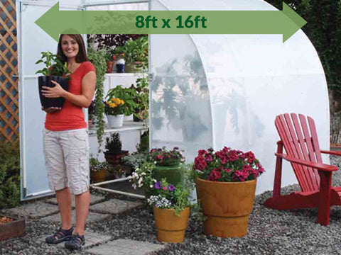 Image of Solexx 8ft x 16ft Harvester Greenhouse G-416 - full view with plants and flowers in and out of the greenhouse - green arrow on top showing dimensions -  a woman outside carrying a pot with plants