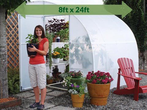 Image of Solexx  8ft x 24ft Harvester Greenhouse G-424 - with plants - in a garden - a woman outside holding a pot with plant