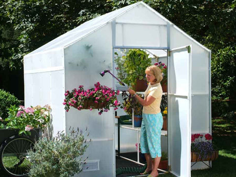 Solexx  8ft x 8ft Garden Master Greenhouse G-508 - side and front view - with plants and flowers and a woman watering the plants