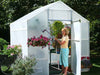 Image of Solexx  8ft x 8ft Garden Master Greenhouse G-508 - side and front view - with plants and flowers and a woman watering the plants