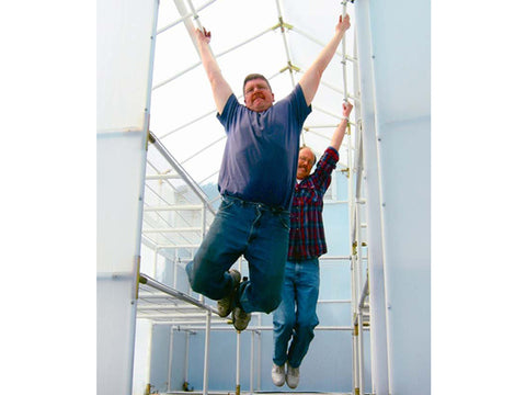 Solexx 8ft x 8ft Gardener's Oasis Greenhouse G-208 - interior view - two people hanging on framework to show how strong the greenhouse is