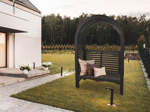 The Adelaide Dove Gray Arbor With Bench and Pillows in a garden