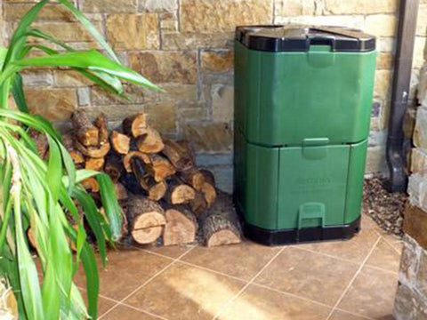 Aerobin 400 Insulated Composter - by the wall with a pile of woods on its side