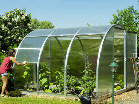 Side view of Arcus Greenhouse with two side panels fully opened - a woman lifting the side panel