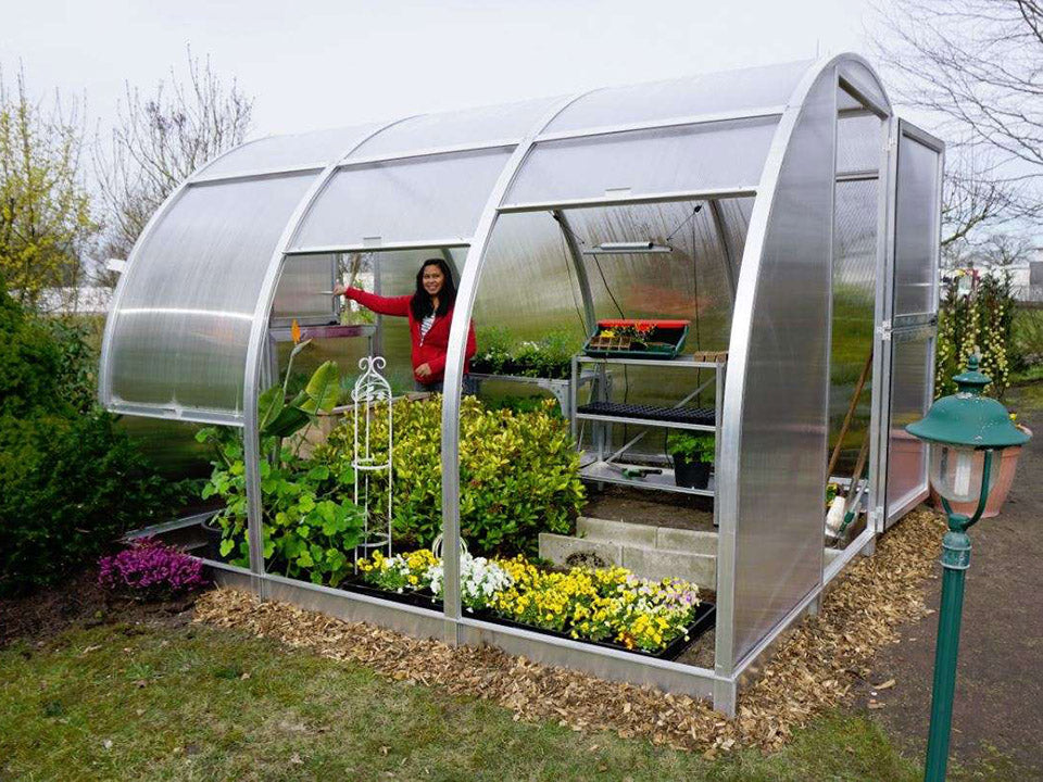 Side view of Arcus 3 Greenhouse - front door fully opened - two side wall sections are lifted the third side wall is slightly lifted - a woman is gardening inside