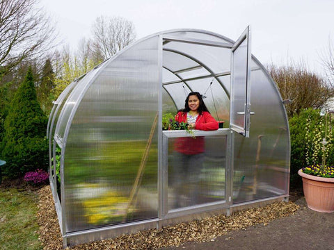 Image of Front view of Arcus 3 Greenhouse - top section of door is open - a woman is standing inside