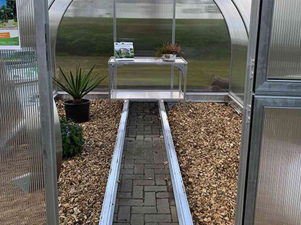 Open door front view of Arcus Greenhouse with plants and a shelf inside