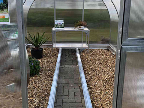 Image of Open door front view of Arcus Greenhouse with plants and a shelf inside